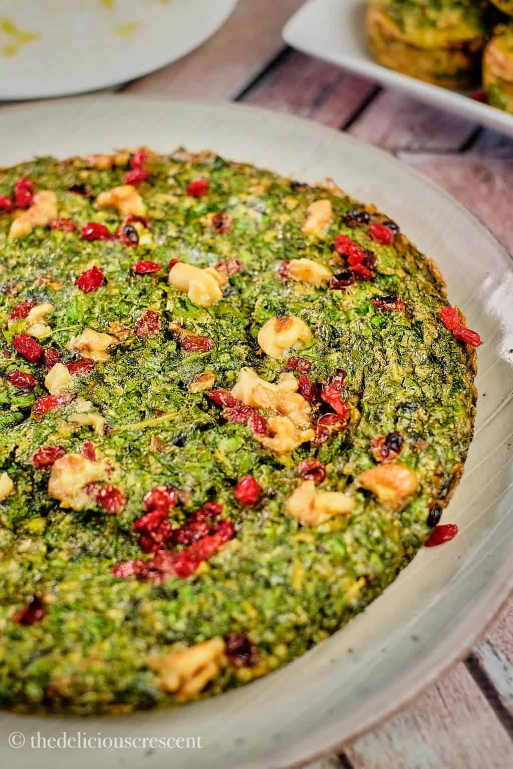 Kuku sabzi placed on a grey plate.