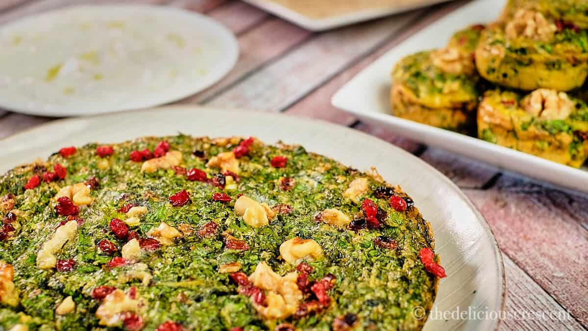 Persian herb frittata in traditional and appetizer muffin style placed on a table.