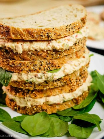Tuna sandwiches made with chipotle stacked on a plate.