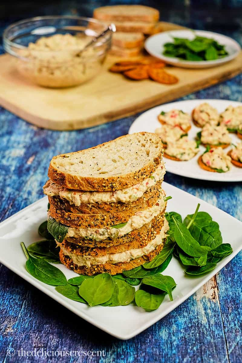 Spicy tuna salad sandwiches and crackers placed on a blue table.