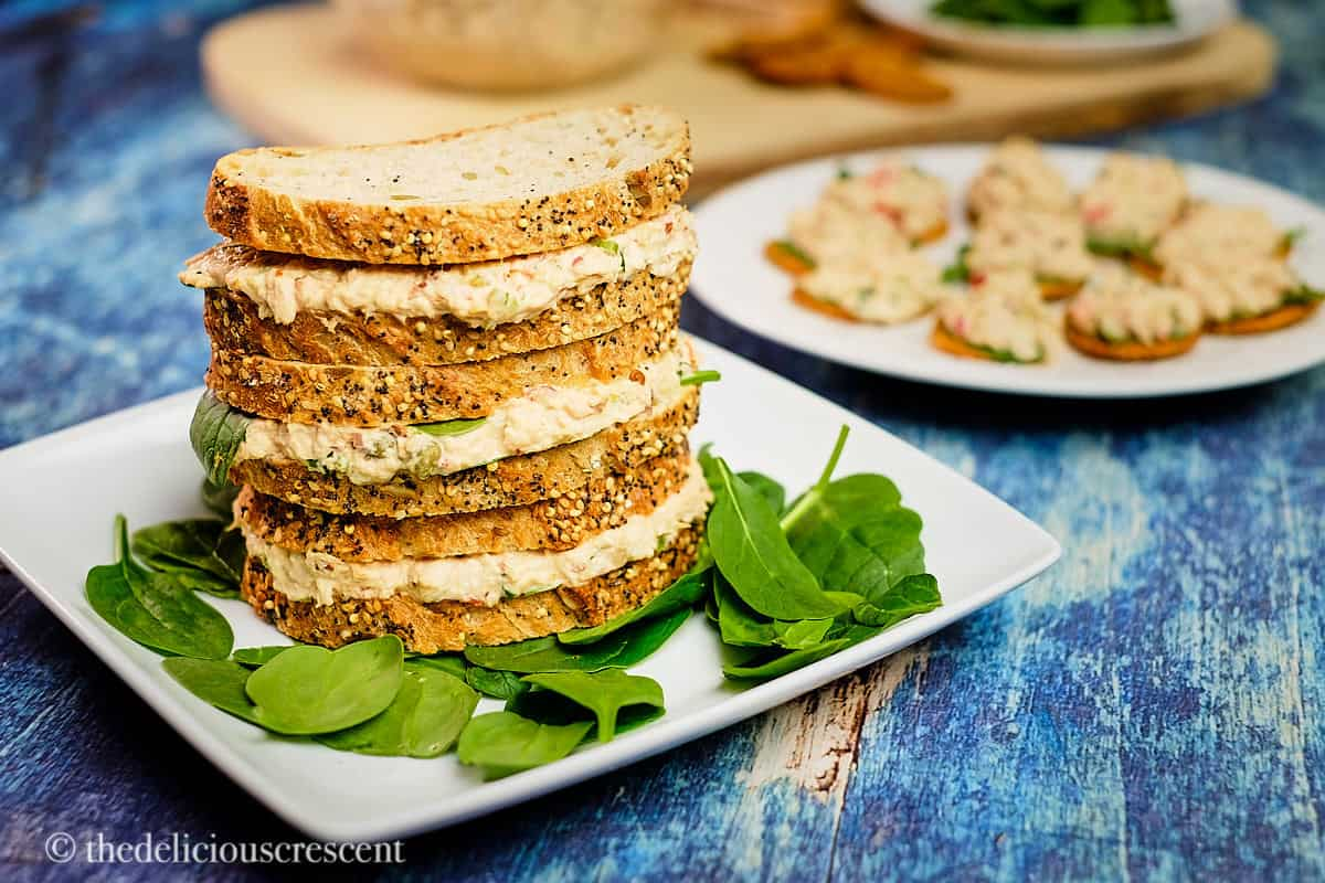 Spicy tuna salad sandwiches stacked on a plate.