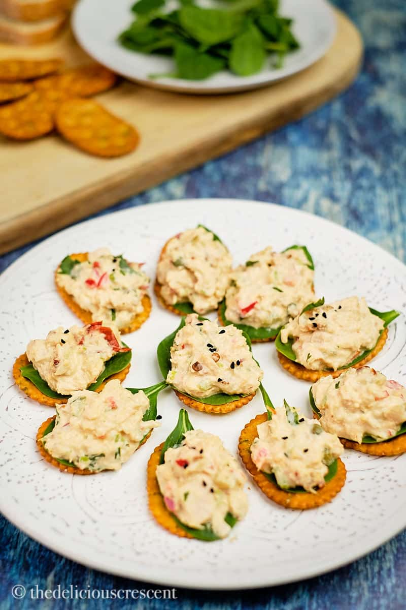 Tuna salad topped on crackers lined with spinach leaves.