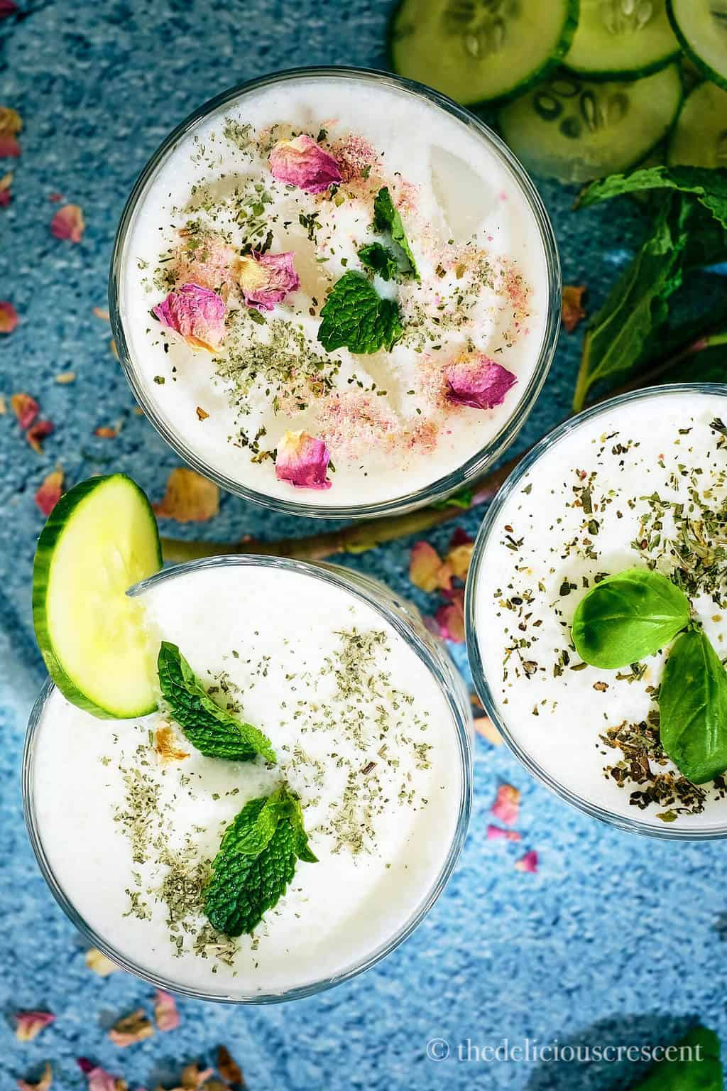 Overhead view of yogurt based beverage topped with herbs and rose petals.