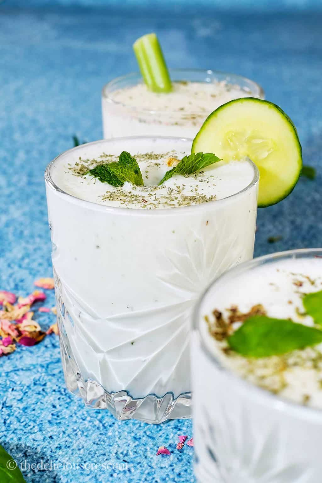 Yogurt drink in a glass with a cucumber slice on the rim.