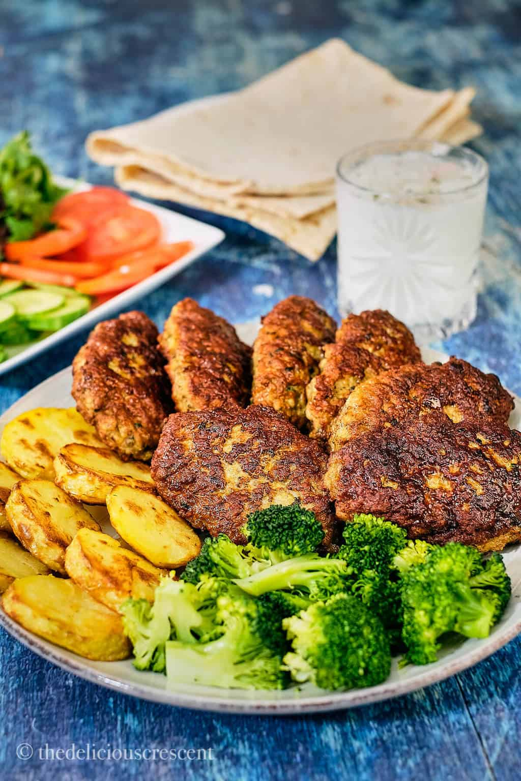 Persian kotlet served with a side of potatoes and broccoli.