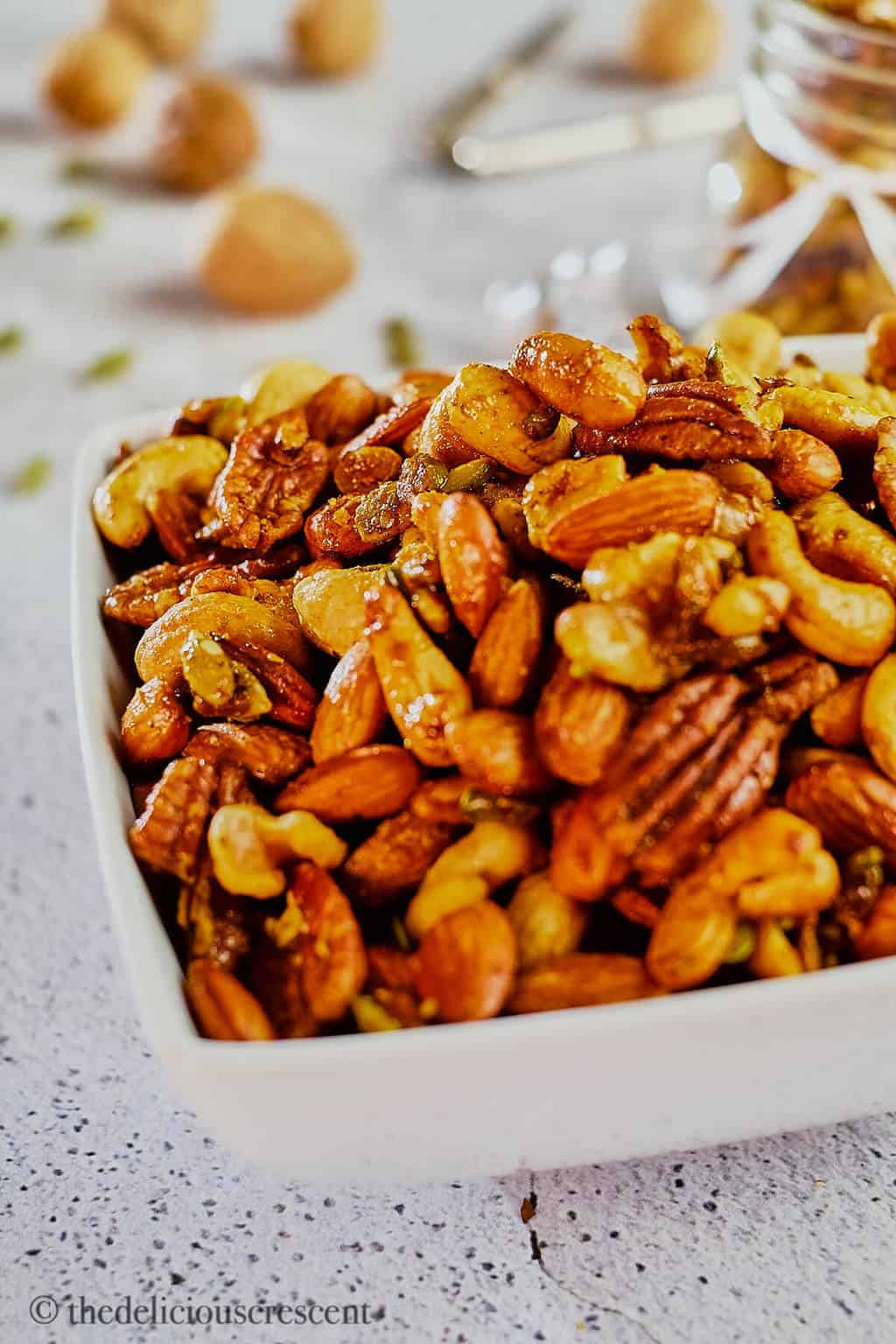 A white bowl full of sweet and savory roasted party nuts.