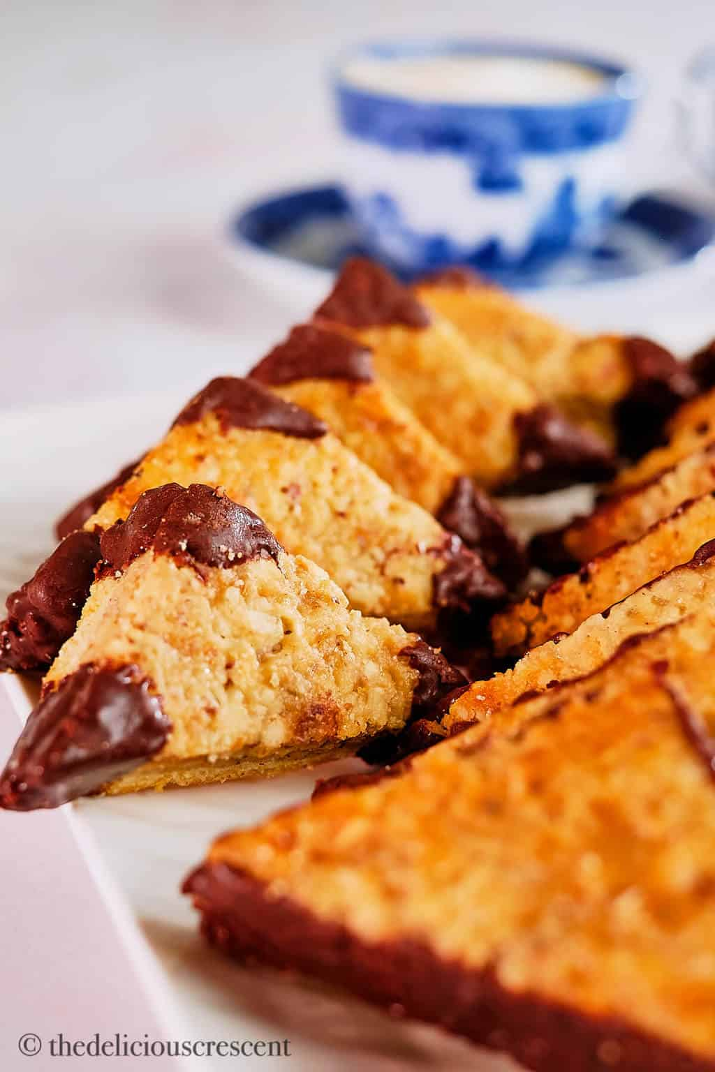 Hazelnut chocolate cookie bars stacked and arranged on a white plate.