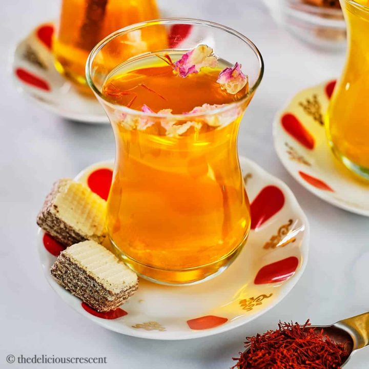 Saffron tea served in a glass cup and placed on a table.