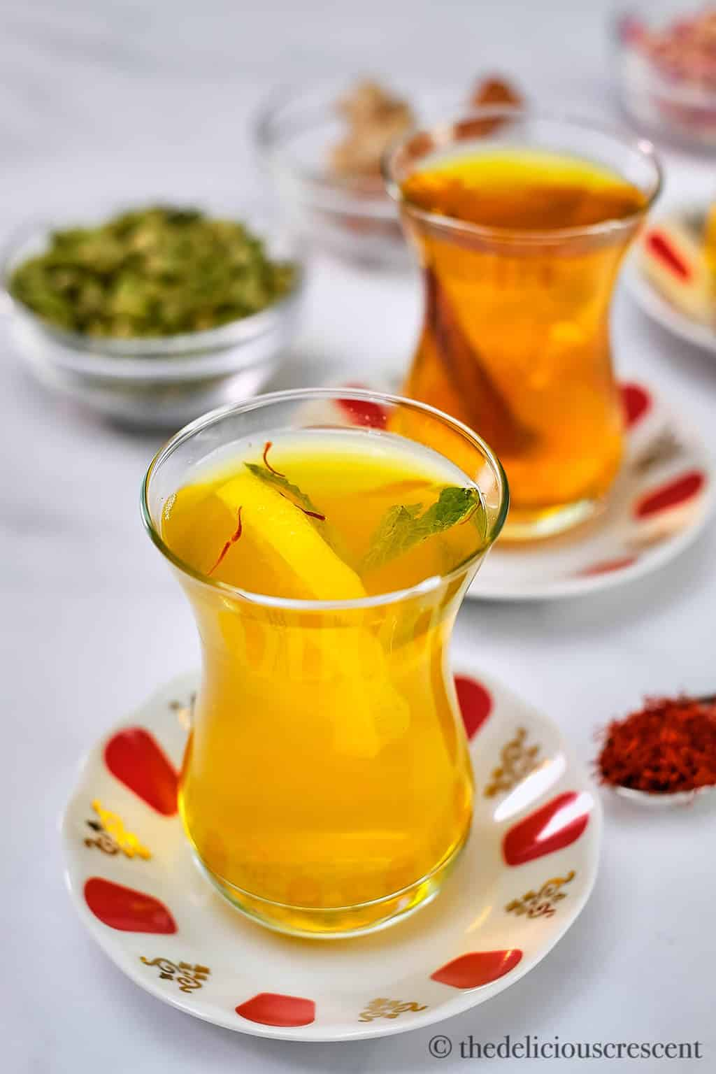 Hot beverage with ginger and mint served in a glass.