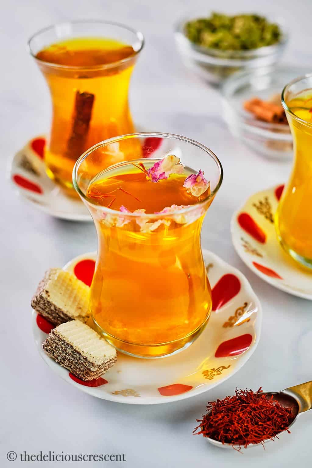 Saffron tea served in glass cups with rose petals, cinnamon and mint.