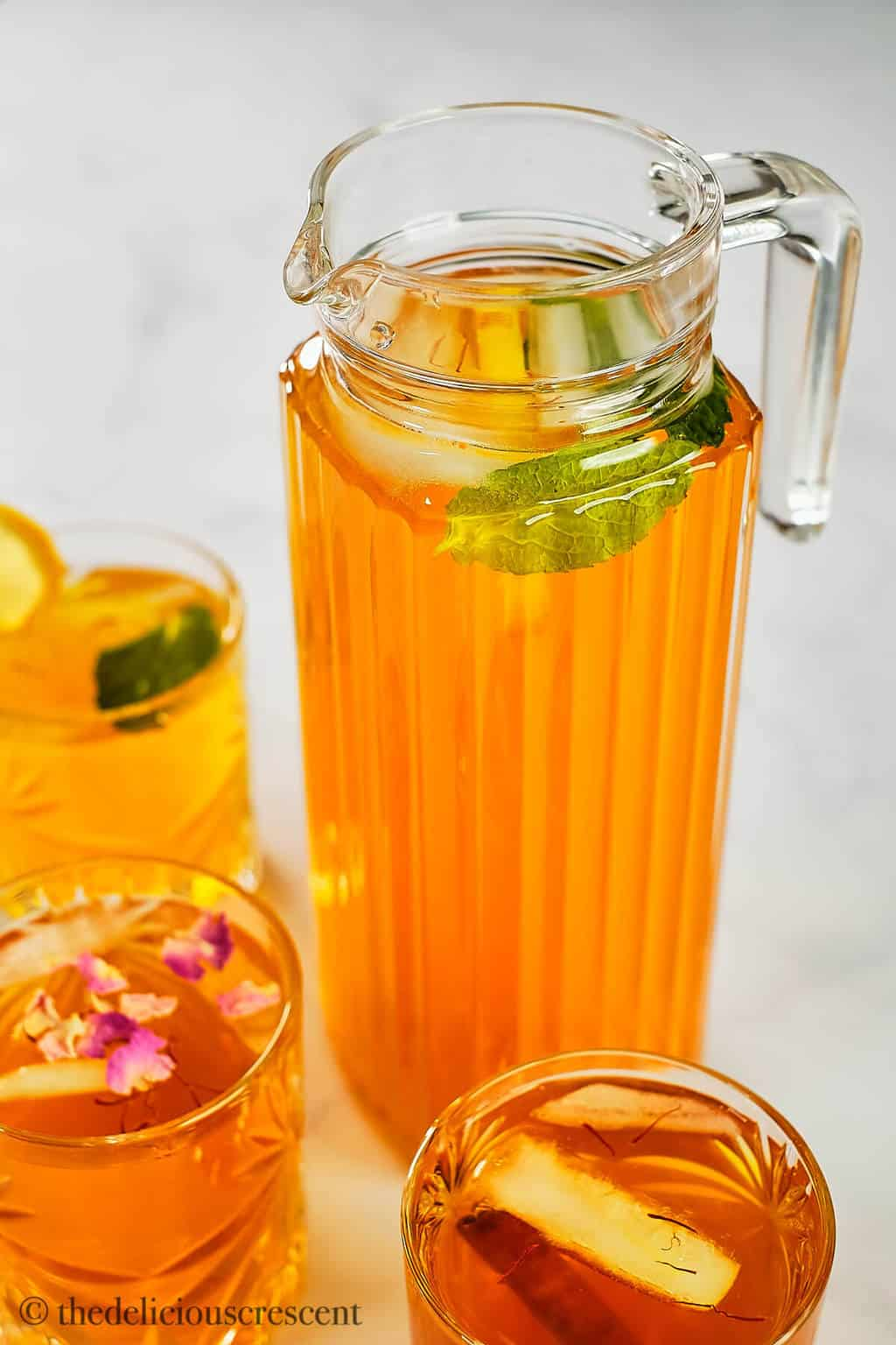 A pitcher full of exotic iced drink prepared with aromatic ingredients.