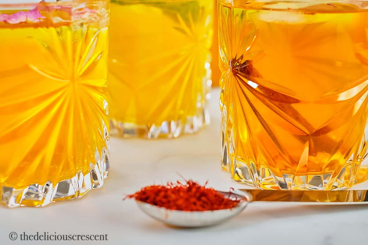 Iced saffron tea with different flavor variations served in clear glasses.