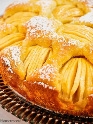 German apple cake dusted with sugar and served on a plate.