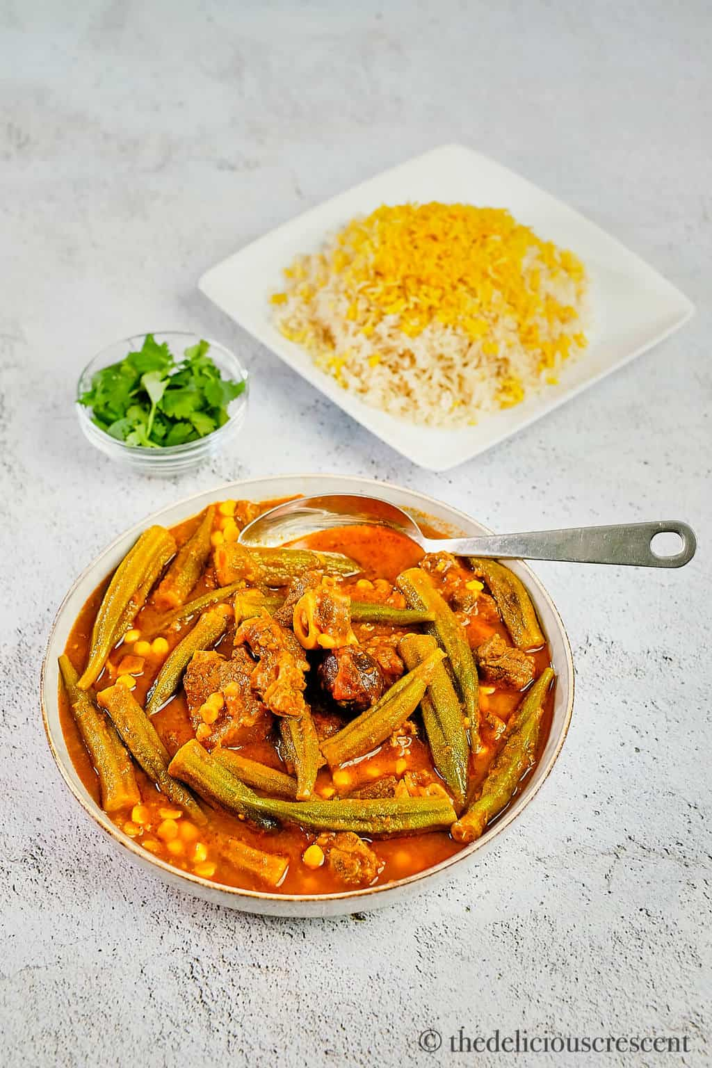 Okra stew with lamb served in a grey bowl with brown rice.