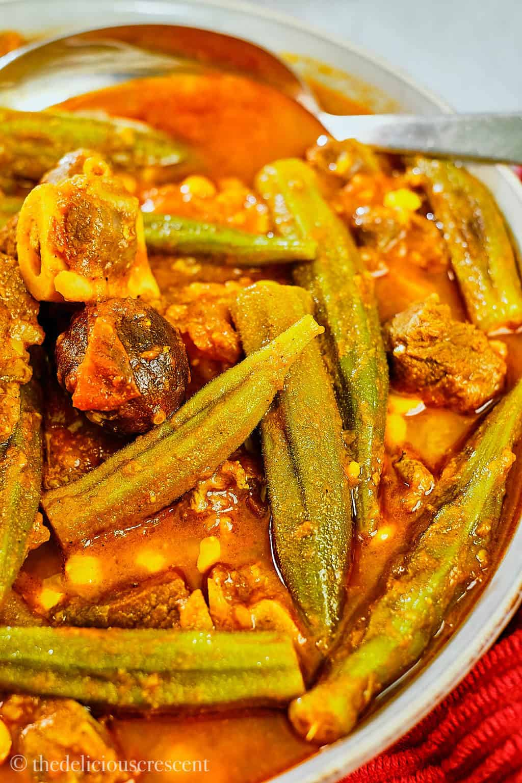 Close up view of okra stew in a serving bowl.