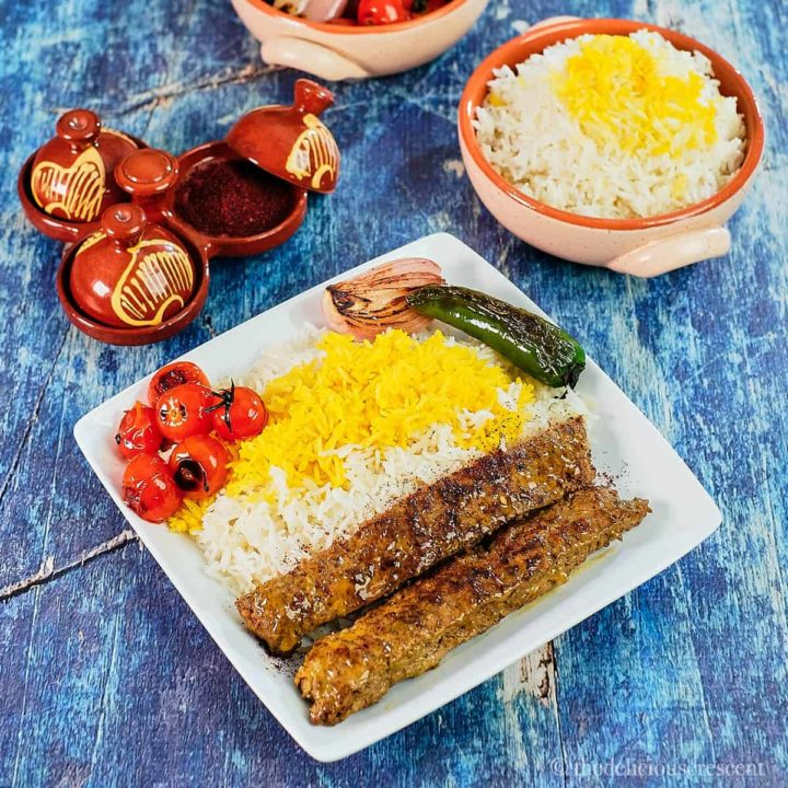 Kabab Tabei served on a white plate with rice and seared tomatoes and peppers.
