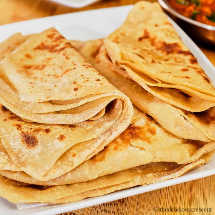 A stack soft parathas on a white plate.