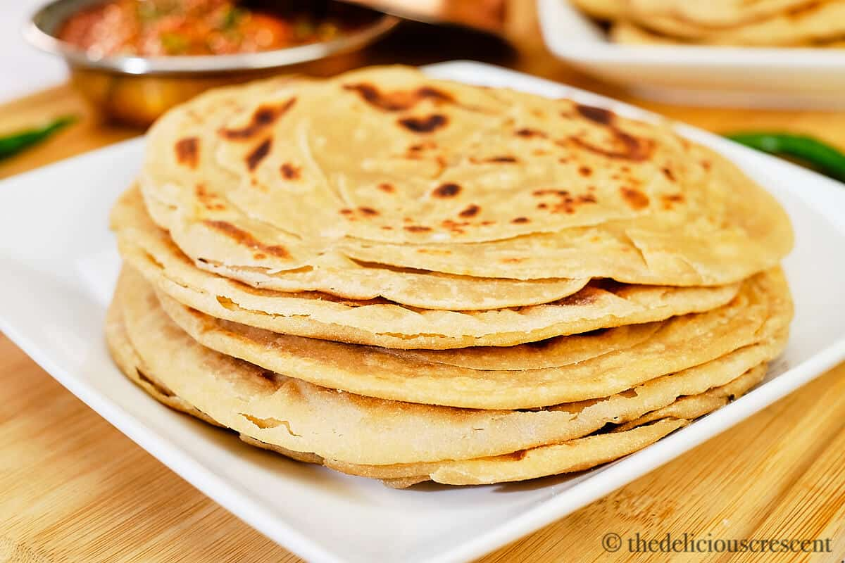 Indian layered flatbread (parathas) stacked on a plate.