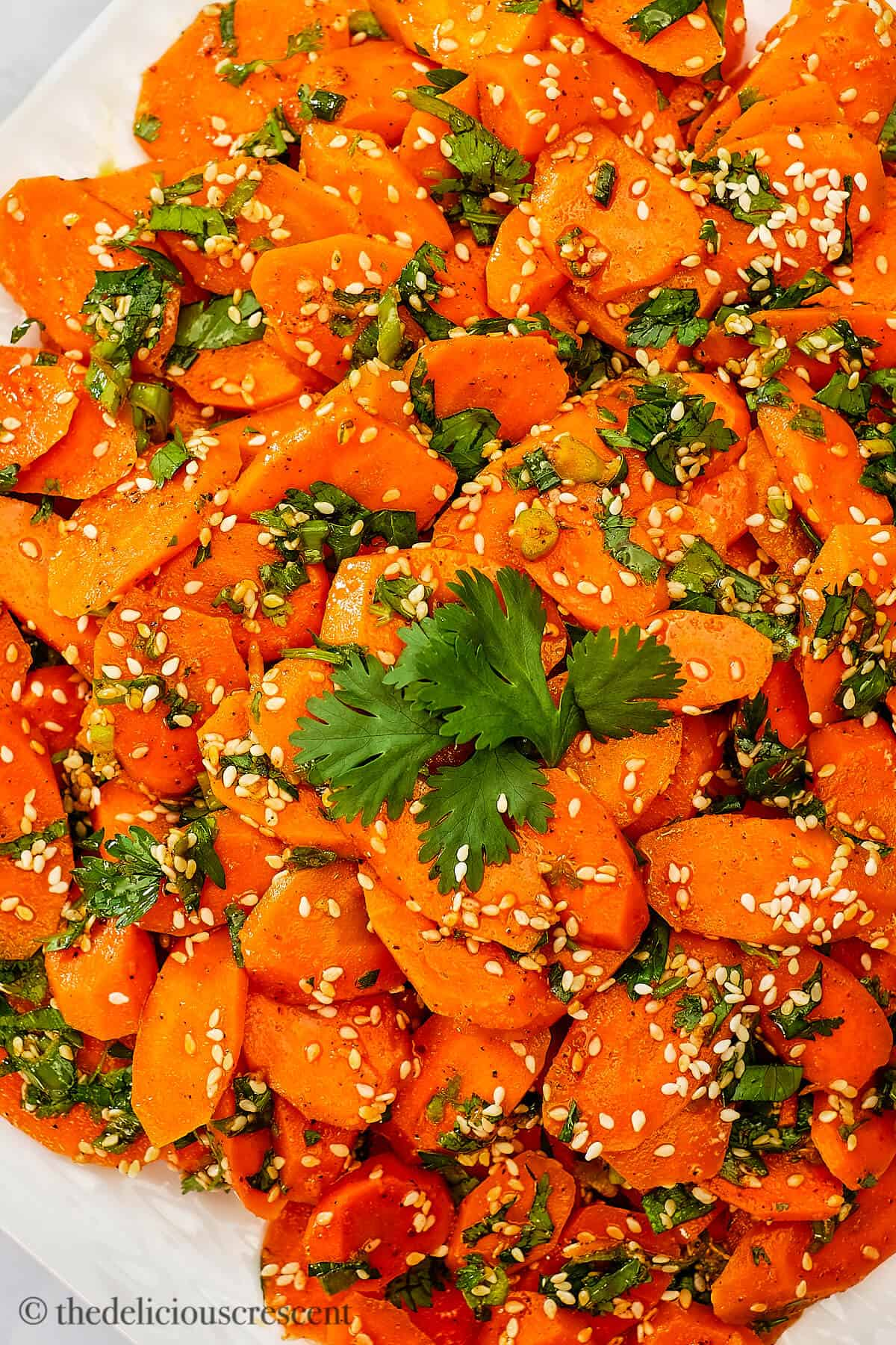 Spiced carrot salad garnished with herbs and sesame seeds.