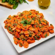 Spicy carrot side dish served in a white plate.