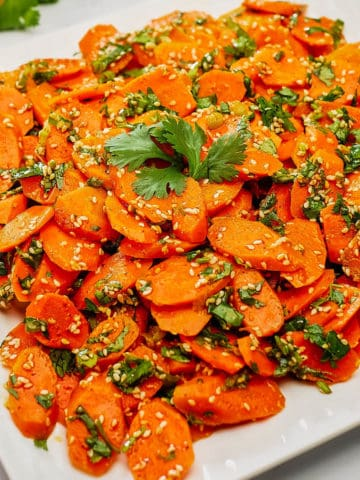 Moroccan carrot salad served in a white plate.