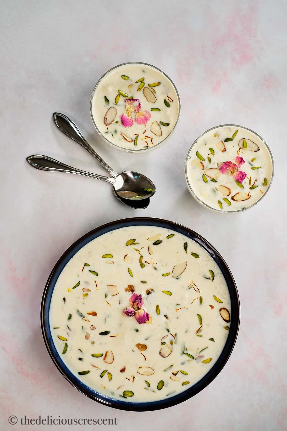 Kheer in a large serving bowl and two small bowls.