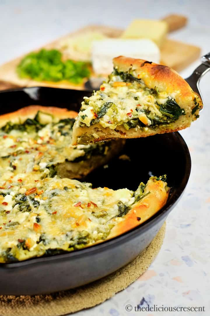 A wedge of spinach feta pizza lifted with a serving utensil.