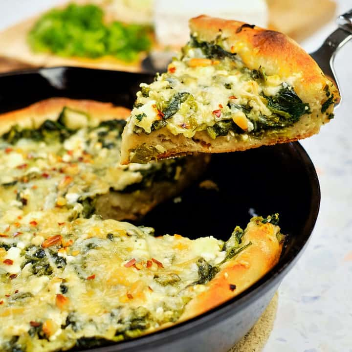 Close up view of spinach feta pizza wedge lifted with a serving utensil.