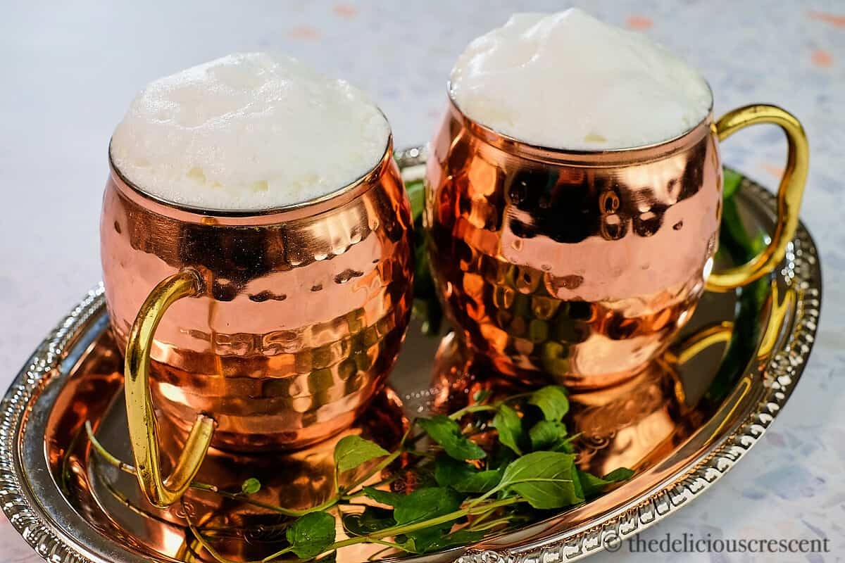 Two copper mugs with Turkish yogurt drink in it.