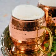 A copper mug full of Ayran with foam on top.