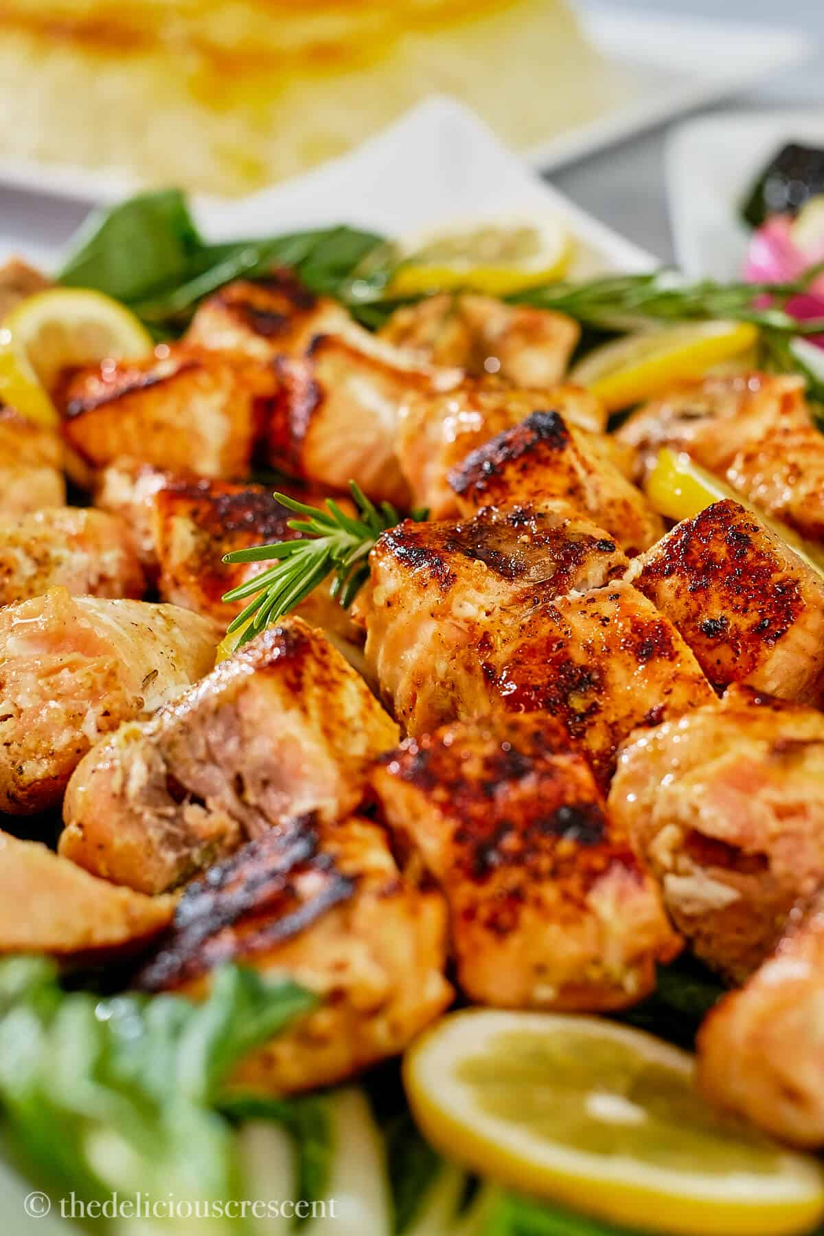 Salmon kebabs with lemon sliced placed on greens.