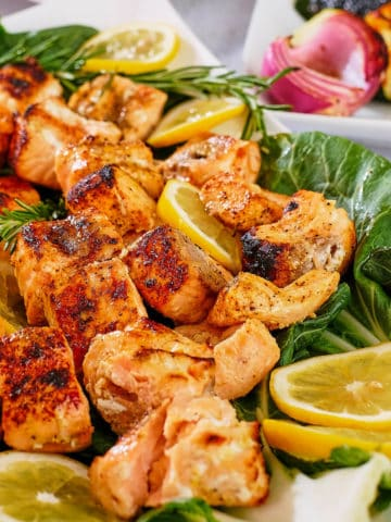 Grilled salmon kabobs and lemon slices arranged on a platter.