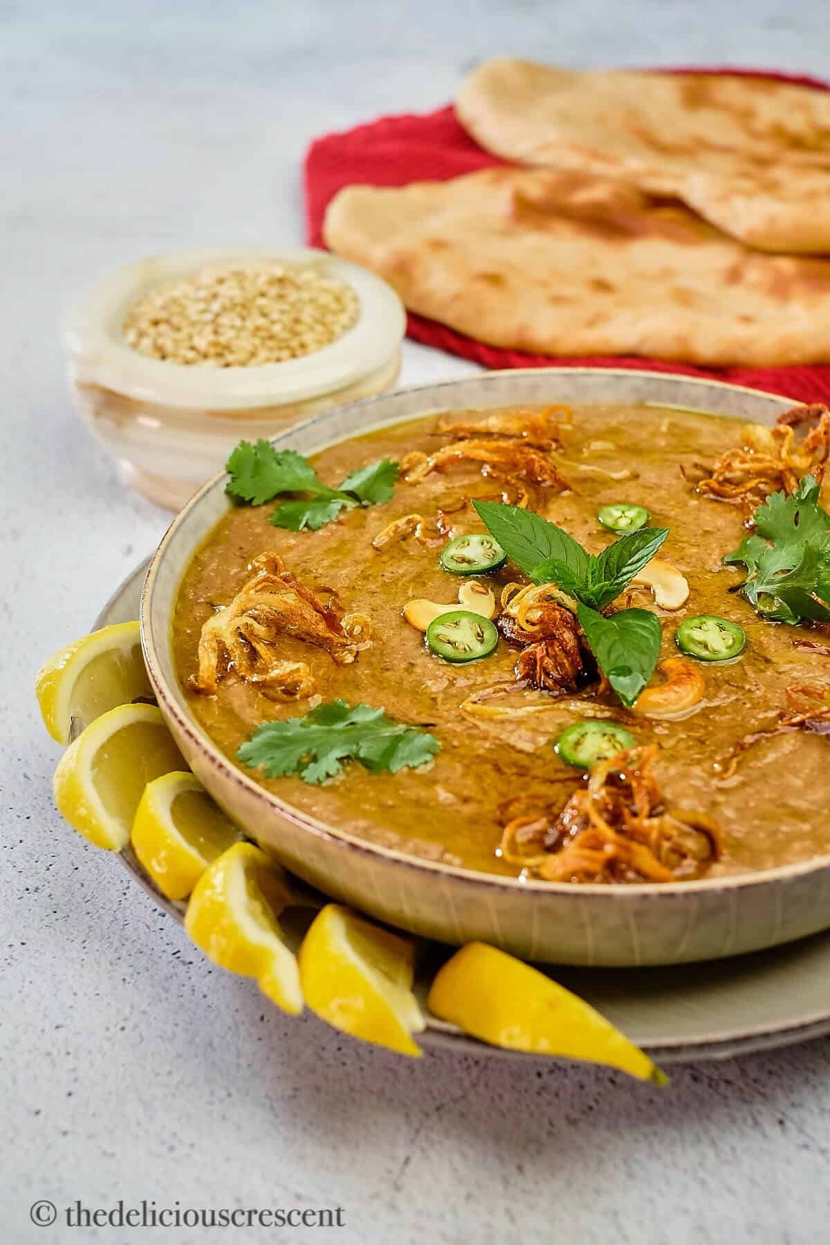 Haleem served in a bowl with lemon wedges and naan bread.