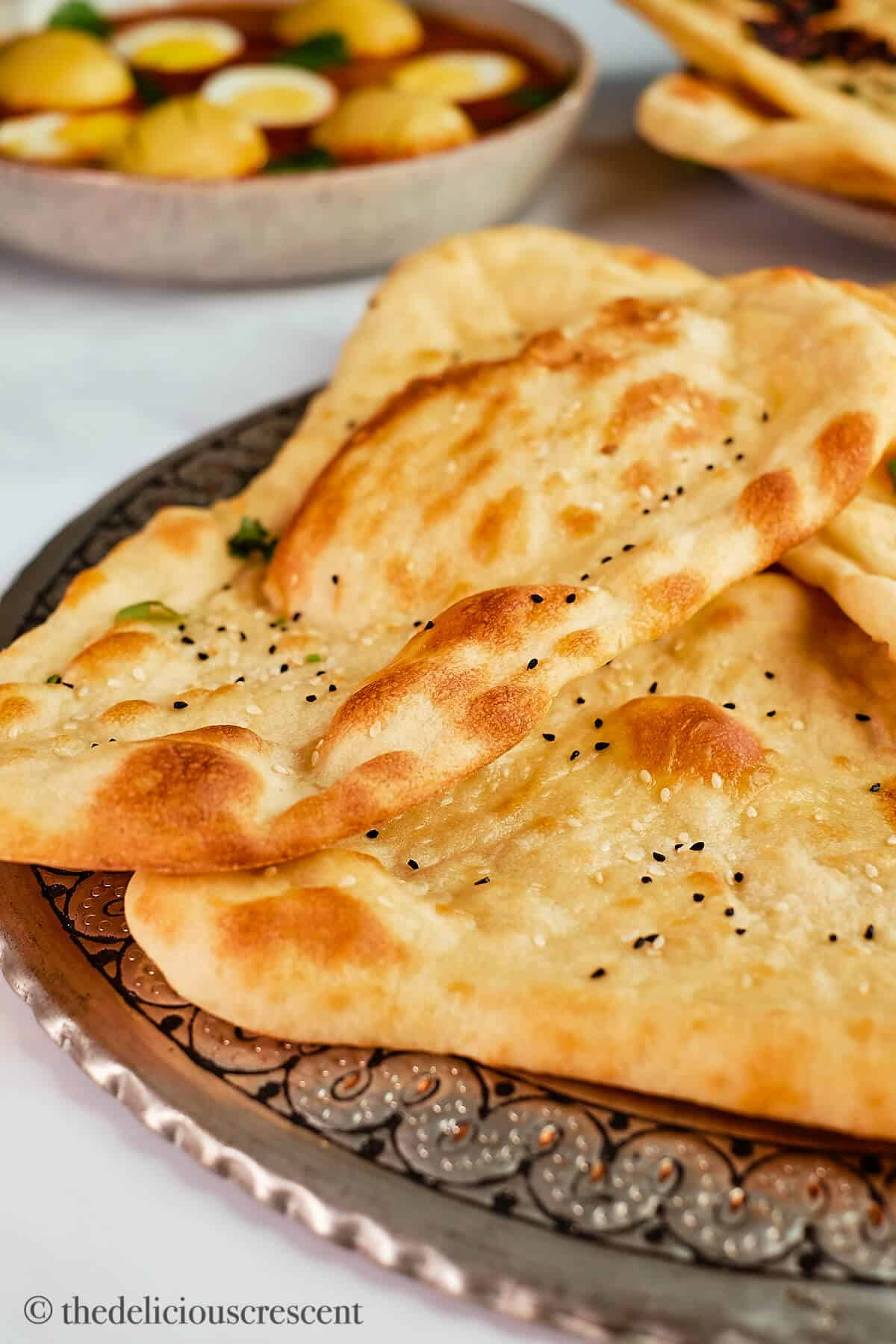 Indian naan placed on a metal plate.