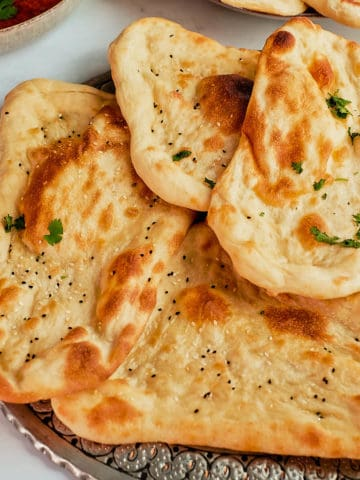 Naan breads arranged on a metal platter.