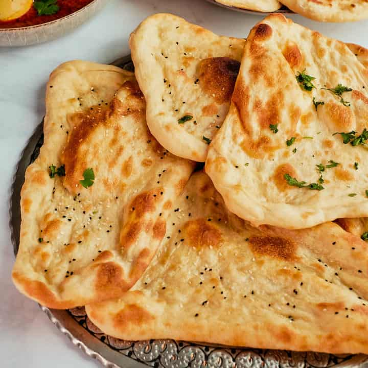 Naan breads arranged on a metal platter.