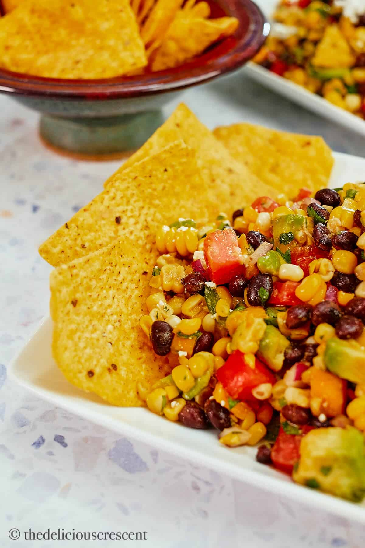 A stack of corn chips placed around corn salad.
