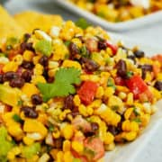 Spicy corn salad with avocado served on a plate.