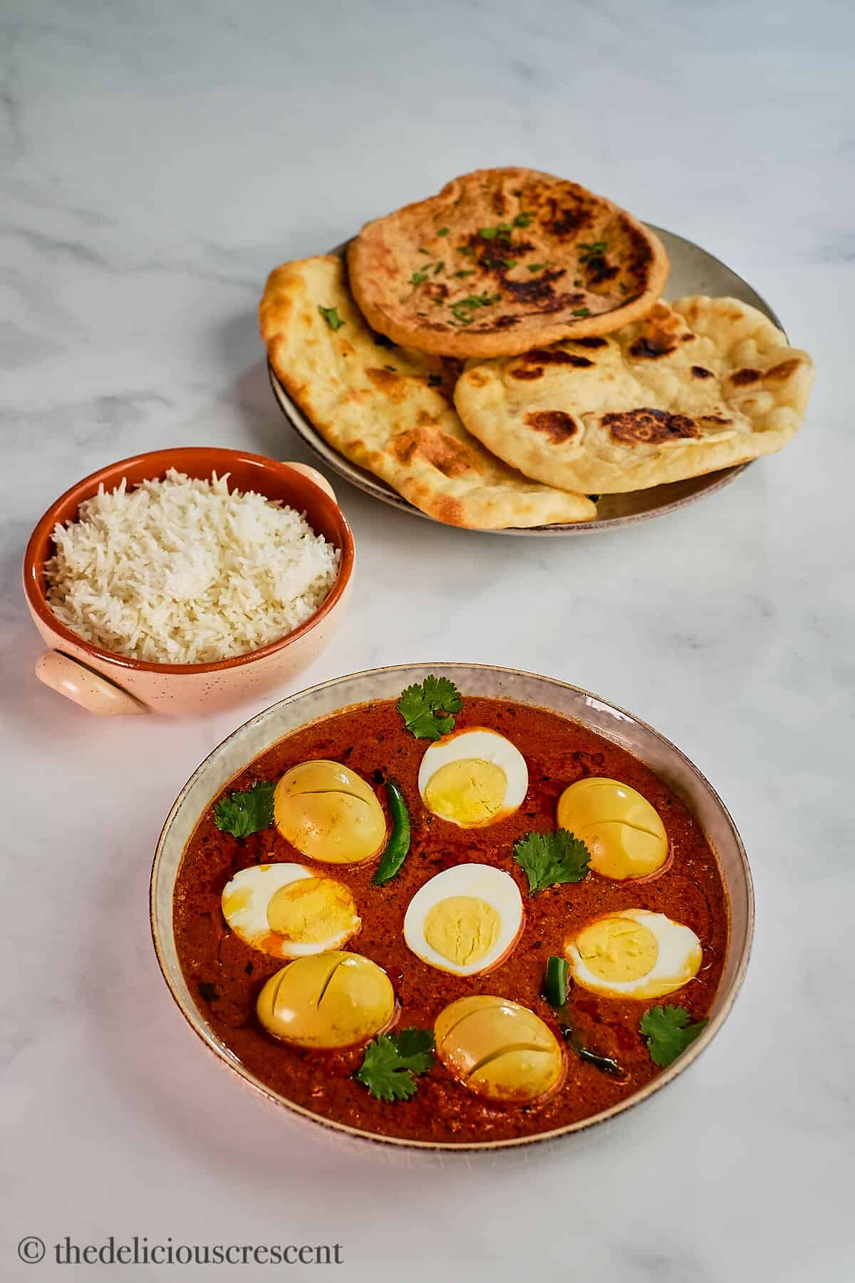 Egg curry served with naan and rice.