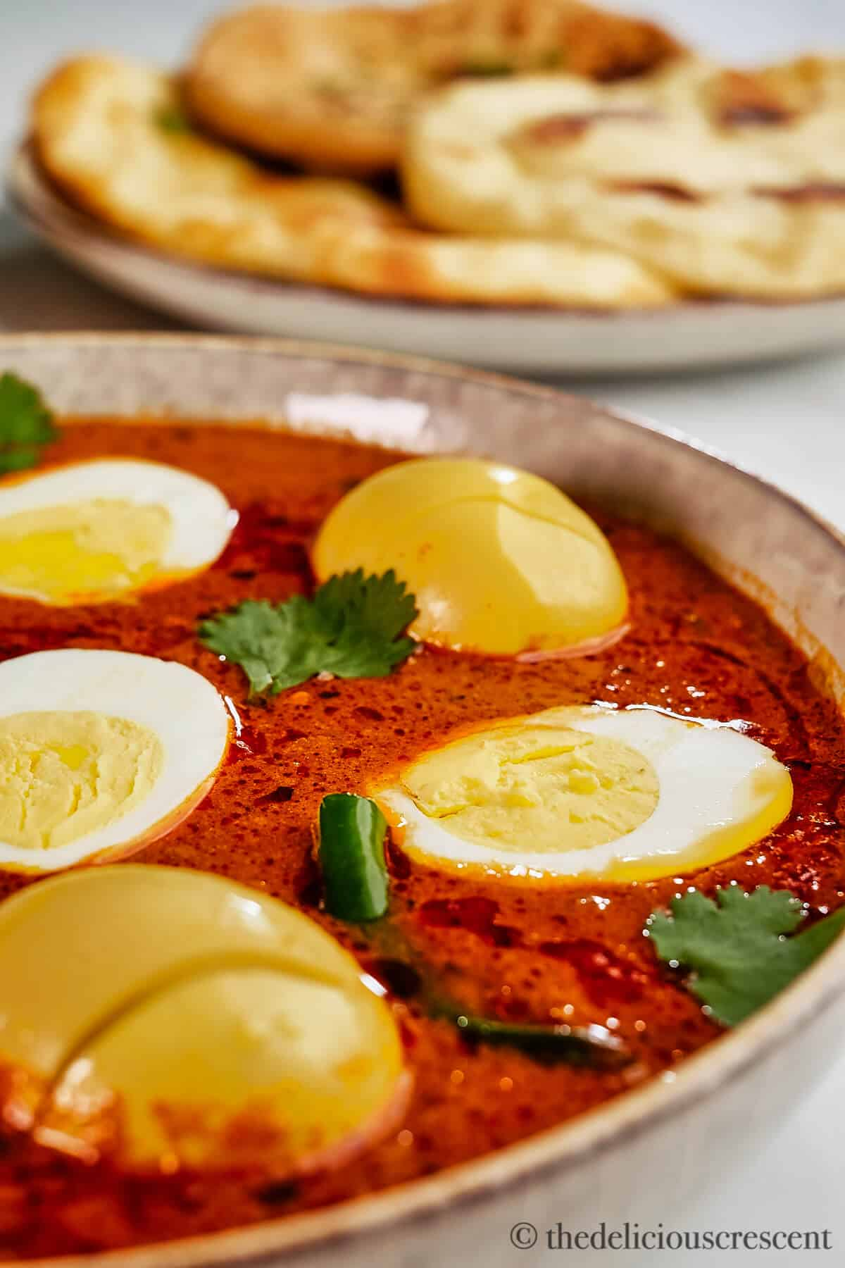 Close up view of eggs in a tomato and onion sauce.