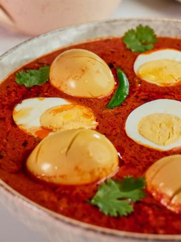 Close up view of eggs in tomato curry served in a bowl.