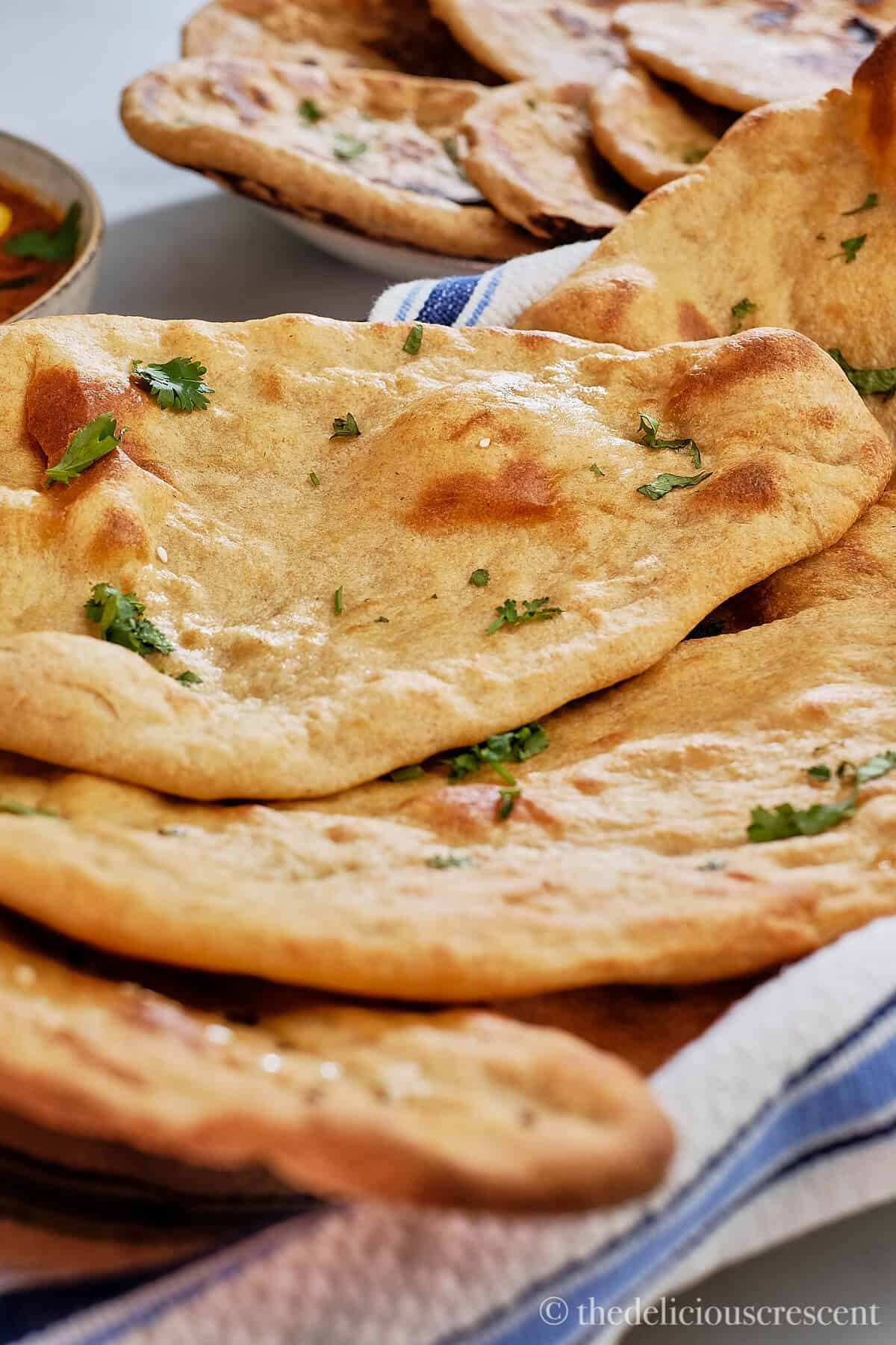 A stack of whole grain naans in a basket.