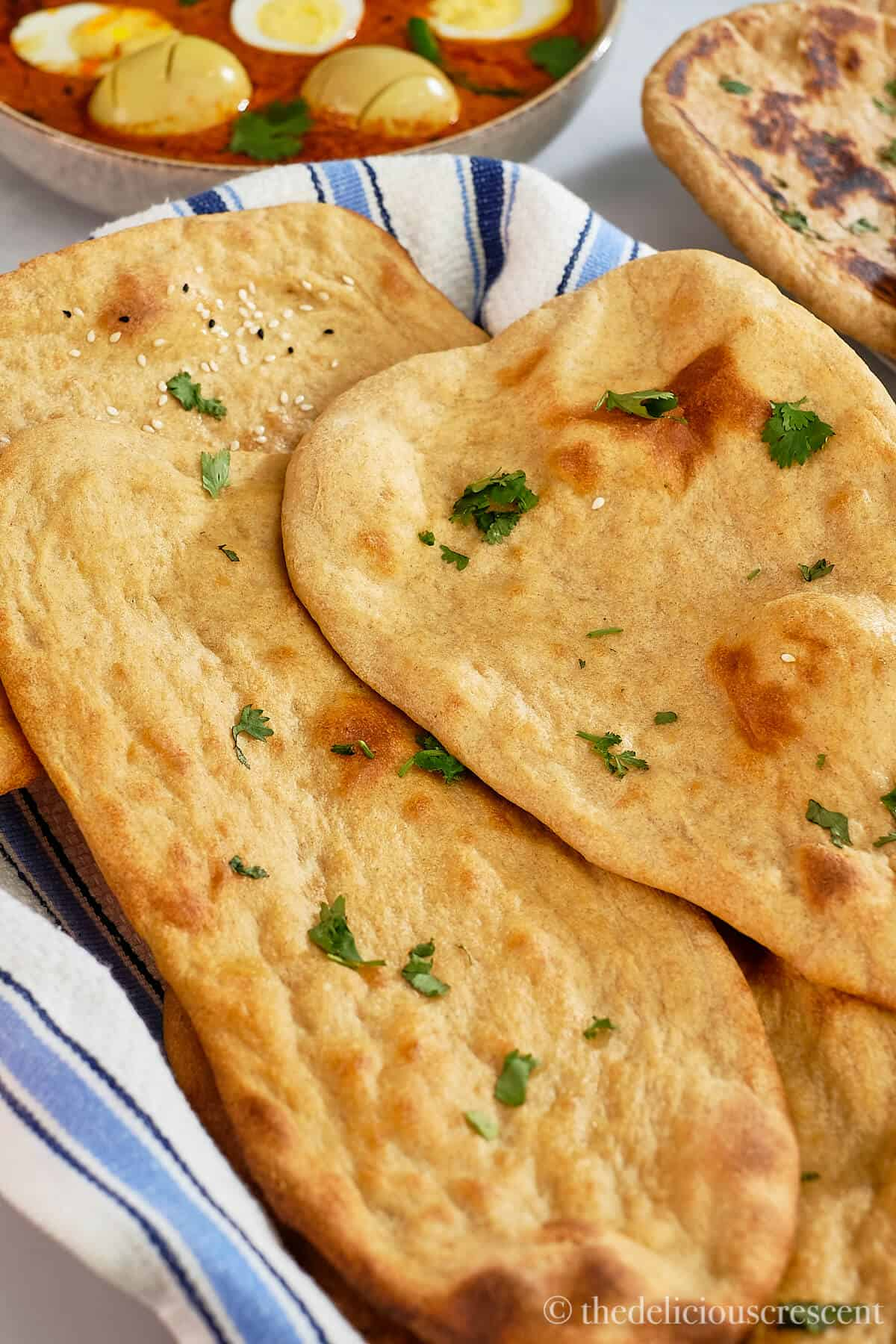 Two whole wheat naans on a kitchen towel.