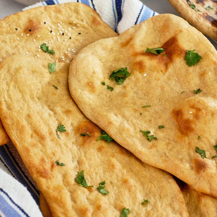 Close up view of whole wheat naans on a kitchen towel.