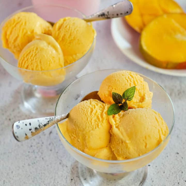 Scoops of mango gelato in glass bowls.