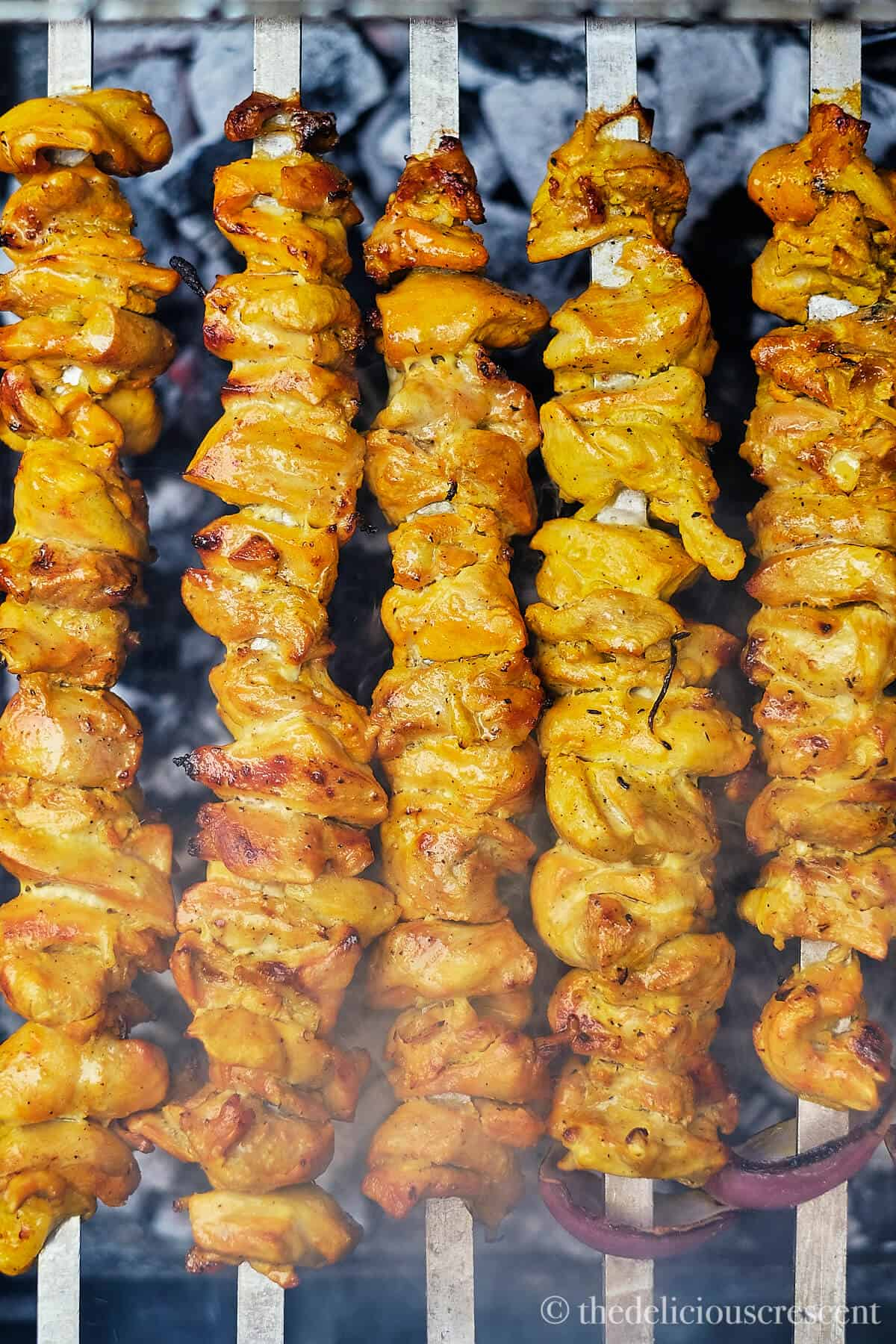 Chicken grilling on skewers.