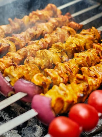 Close up view of Persian grilled chicken kabobs on skewers.