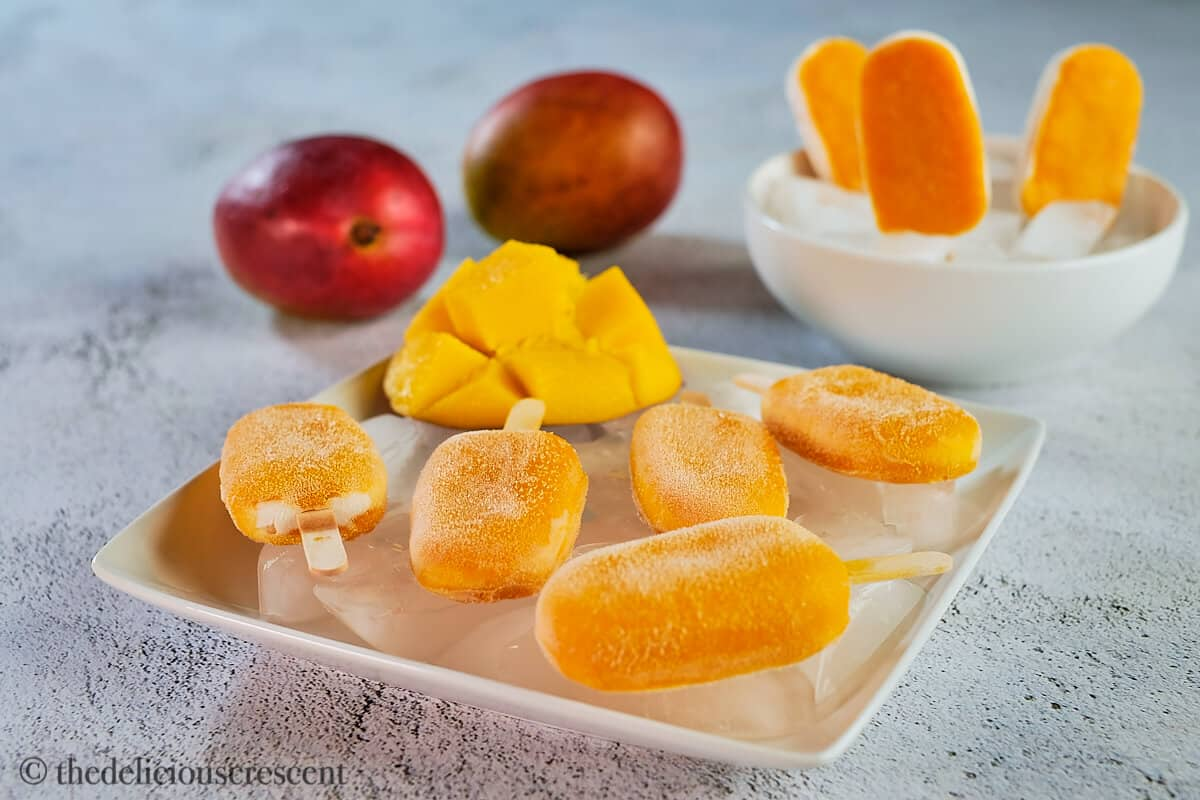 Several mango popsicles on a plate.