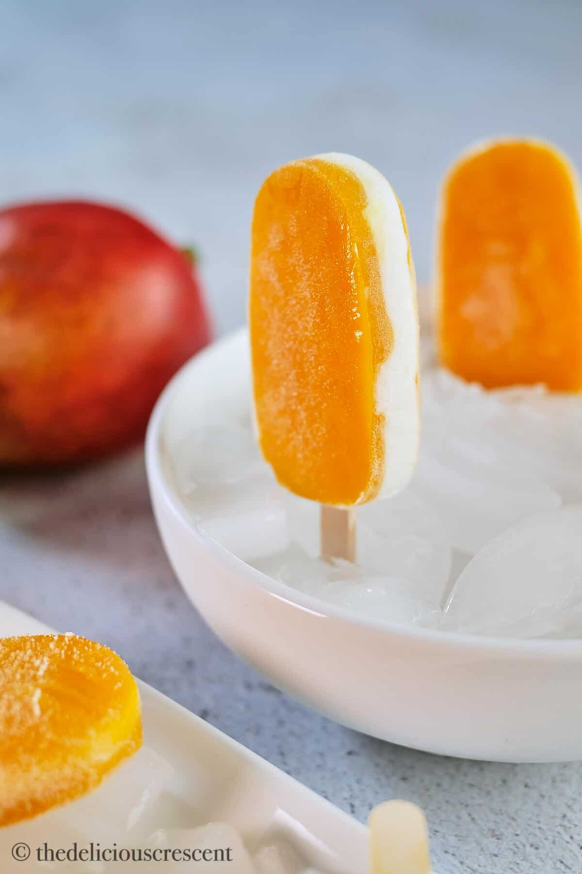 Creamy vanilla filling in the middle of two mango layers in an ice pop.