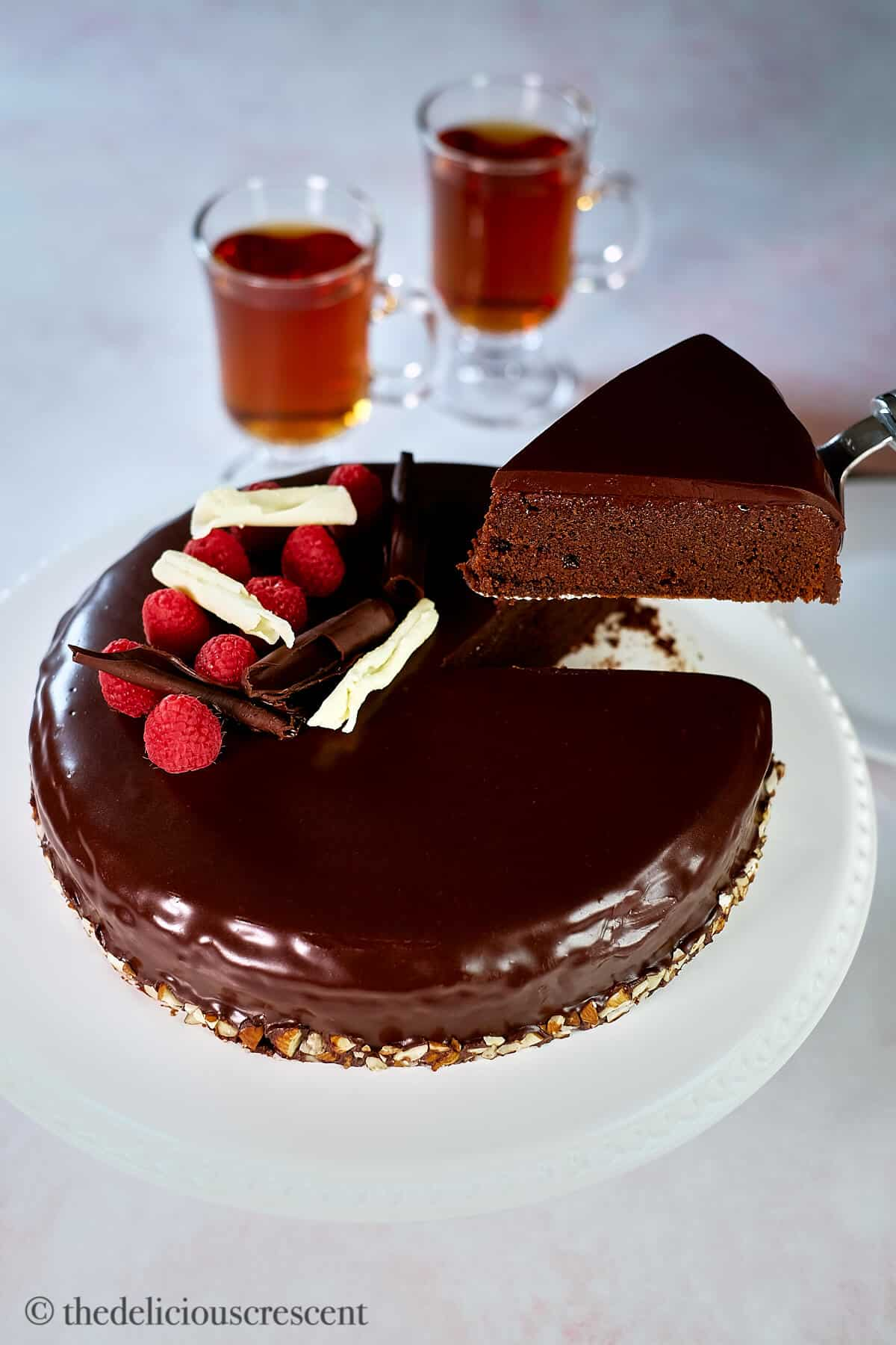 A piece of chocolate almond cake being lifted with a serving utensil.